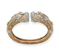 A GOLD AND DIAMOND 'CHIMAERA' BANGLE, BY CARTIER  The textured gold bangle with variously cut diamond detail with facing chimaera terminals, 5.5 cm wide, with French assay marks for gold and platinum