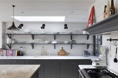 Gray and white London kitchen renovation, shelving inspired by French bistros, Remodelista