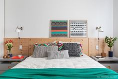 Quarto de casal com estilo escandinavo tem cabeceira de pinus, criado mudo na cor cinza e almofadas de tricô.