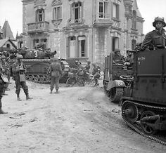 British Universal Carriers with deep wading screens and a Churchill AVRE tank passing through La Breche. 6 Jun 1944