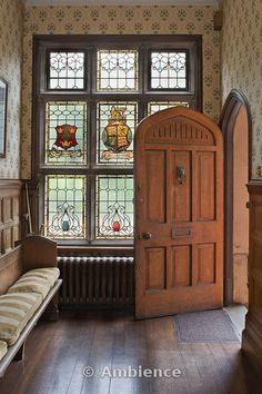 Entrance Hall with stained glass window with heraldic crests, arched door and wooden settee in Nottingham.