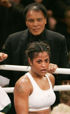 U.S. boxing legend Muhammad Ali (top) smiles as he stands behind his Daughter Laila Ali, after her super-middleweight fight against Asa Sandell of Sweden in Berlin December 17, 2005