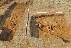 A photo of two human skeletons being excavated from a brown pit at a Roman villa site in Northamptonshire