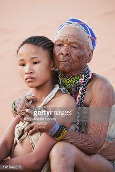 Photo : Indigenous Bushman/San girl embraced by grandmother (14years Les Bushmen de la Réserve du Kalahari central au Botswana sont les derniers chasseurs d'Afrique. En 2006, ils ont gagné un procès contre le gouvernement, les autorisant à retourner sur leur territoire ancestral après en avoir été expulsés de force.  L'histoire aurait pu s'arrêter là, mais le Botswana continue de persécuter impitoyablement et sans relâche ses premiers habitants afin de les chasser de l, 75 years old)…