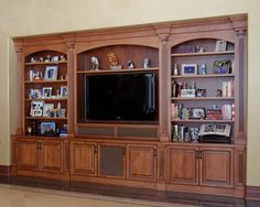 A well-designed built-in entertainment center is a great way to display photos and mementos and to hide unsightly audio equipment! Special mesh inserts in select doors of this entertainment center conceal speakers without sacrificing sound quality.  #speaker #cloth #stereo #custom #wood #stained #entertainment #system #tv #television #storage #display #cabinet #built-in #built #in #crown #moulding #valance #arched