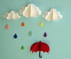 Arco iris-coloreado las gotas de lluvia caen de las nubes por encima de un paraguas rojo poco en este arte de la pared 3D adorable. Cada pieza del arte de la pared está separada de los demás lo que le permite colgar en la pared y organizar sin embargo que desea y se puede mover tan a menudo como usted tiene gusto. Añadir textura y dimensión a la pared y son el toque perfecto en un vivero, Habitación infantil o sala de juegos.  Arte de la pared se compone de 7 tres gotas de agua…