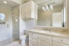 6631 Edloe Southside Place, TX 77005: Photo En suite bath with porcelain tile floor, custom cabinetry, marblecounter, walk-in shower with porcelain tile and marble hexagon detail