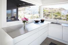 Køkkenet er skarpt skåret ligesom resten af sommerhuset. Elementerne er fra Svane Køkkenet. Bordpladen er 6-mm's massivt, rustfrit stål, og pladen er specialfremstillet til huset.