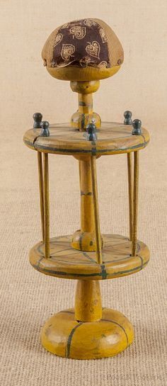 "Painted pine revolving spool holder, 19th c., with a pincushion finial, retaining its original blue star decoration on a yellow ground, 11 1/2"" h."