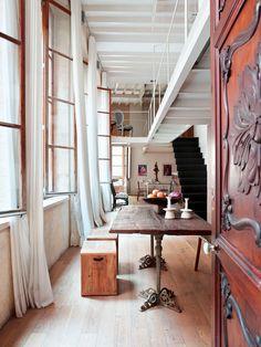 Una casa con mucho arte ZONA DE COMEDOR Sobre la mesa antigua, con sobre de madera y patas de hierro, candeleros de Luzio Palma y los bancos proceden de un desembalaje en Francia. Las cortinas de lino crudo, de Designers Guild, colocadas de suelo a techo unifican toda la estancia.