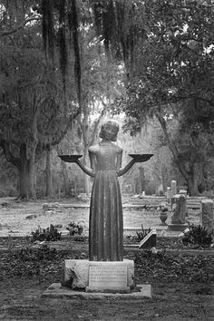 """""""The Bird Girl"""", as this icon is known locally in Savannah, GA, is a 1936 bronze sculpture by Sylvia Shaw Hudson and once serenely presided over a private family plot in the city's historic Bonaventure Cemetery. It is now installed at the Telfair Museum of Art. This move was necessitated after her photograph was featured on the cover of the bestselling book, Midnight in The Garden of Good and Evil by John Berendt in 1993, after which time her notoriety soared as a landmark."""