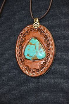 Turquoise triangle in tooled leather oval. Set by hand in wood tone briar brown leather; hand tooled, hand laced for that human touch. on Etsy, $78.00