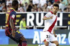 El jugador del Barcelona Alex Song, trata de controlar el balón en presencia del jugador del Rayo Vallecano Alberto Bueno
