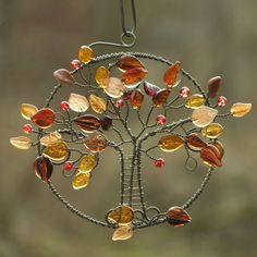 Podzim.     Drátovaný obrázek stromečku, podzimní jabloňky. hnědé a okrové skleněné lístečky a červené bobulky - jablíčka, železný drát.  Průměr kruhu, v němž je stromeček usazen, měří 12 cm, celkové rozpětí obrázku měří cca 16 cm.  Na zeď, do okna, na starou skříň. Drát získá ve vlhku rezavou patinu.   original smu
