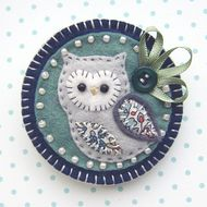 This is a lovely handmade fabric owl brooch.  It features a little felt owl with appliqued wing and belly in lovely Liberty print fabric. It is mounted onto a soft green felt base which is edged with cream seed beads. It is further mounted onto a navy ...