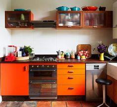 Photograph: Jan Baldwin. The Formica kitchen is inspired by the burnt copper of a Le Creuset pan, matched by a rich brown flagstone floor. Worktops are former school science benches, complete with graffiti.