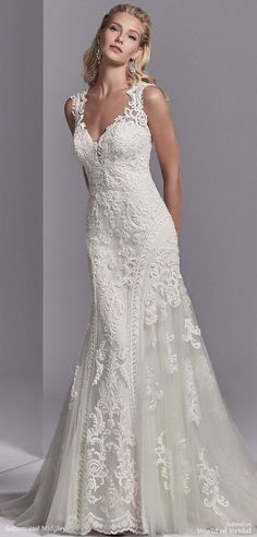 This wedding dress features striking lace motifs accented in beading atop tulle. Embroidered lace borders the tulle on either side of the fit-and-flare skirt. Featuring an illusion plunging sweetheart neckline, illusion straps, and an illusion open back, all accented in lace motifs. Lined with shapewear for a figure-flattering fit. Finished with covered buttons over zipper closure.