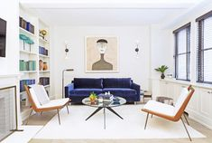 Bright living space with a blue velvet sofa, modern sconces, and matching armchairs