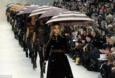 Putting on a show: Model Cara Delevigne, sister of socialite Poppy, led the models on the catwalk, holding umbrellas as faux snow fell @ London Fashion week Burberry Runway Show