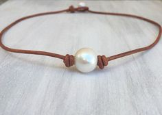 Simple yet elegant freshwater pearl necklace/choker on a soft natural light brown 2 mm leather cord This necklace is made with a beautiful 14 mm high luster freshwater pearl. For the clasp I used a 9 mm freshwater pearl.  Available in : 16 inches  18 inches  20 inches  Please select your size from the scroll down menu.  Each individual necklace may slightly vary in appearance due to the use off al natural materials.