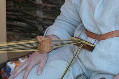 A simple belt holder for backstrap tablet weaving, demonstrated at Haithabu (Hedeby) Viking Museum.