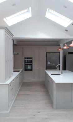 A beautiful example of one of our handmade bespoke kitchens finished in a soft grey with white quartz worktops, undermounted sink and copper light pendants White Kitchen Worktop, Grey Shaker Kitchen, Gray And White Kitchen, Shaker Style Kitchens, Kitchen Worktops, Kitchen Floor, Kitchen Cupboards, Kitchen Room Design, Modern Kitchen Design