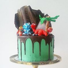 How sweet is this dinosaur drip cake by @sallycakes_1 I must confess to never really thinking of drip cakes for themes like this but it works so incredibly well! #mycupcakeaddiction @elise_strachan