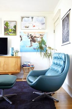 Love the retro blue chair and watercolor art.