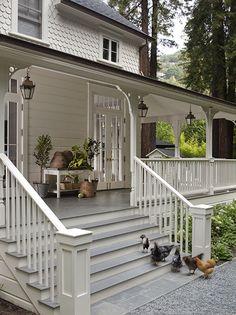 White Farmhouse - Wraparound Porch with Hanging Lanterns - beeskeps on bench