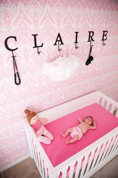Beautiful pink damask wallpaper accent wall in the nursery!