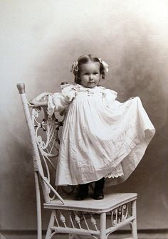 Little dressed up girl standing on wicker chair