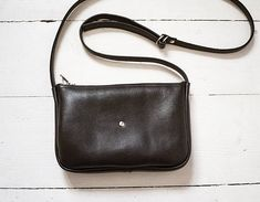 A small, elegant, minimal crossbody bag. Holds whatever you may need it to hold, phone, coin purse, card holder, usb, a few keys, etc. Made of genuine soft black leather. Close with zip. No lining. Adjustable strap. Dimesions: height: 14 cm witdht: 21 cm depth: 2,5 cm strap : up to 125 cm  Possibly to make in other colours. Feel free to write to me. Ready to ship in 2-3 working days.  Standard delivery time:  European union: 4 - 10 days  Europe (not EU): 7 - 14 days  U.S.A., Canada: 10 - 20…