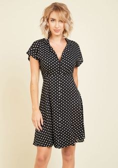 <p>Standing at the door in this black shirt dress, you greet your guests for a night of artistic camaraderie. With a vintage-inspired allure reflected in its subtly gathered empire waist, swingy skirt, and white polka dots, this back-tied frock is a look that rocks from the living room acoustic set to the basement stage!</p>