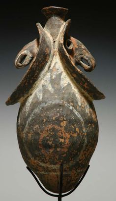 "ritual vessel from the Kwoma culture of the Washkuk Hills north of the Middle Sepik River in Papua New Guinea. The pot has two expressive faces with long noses and big smiles. The pieces comes from the collection of Reg and Judy MacDonald, stands 18 ½"" in height."