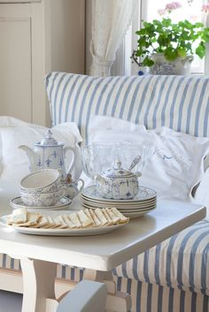 Tea time in blue and white at the beach. Love the stripes of the sofa!