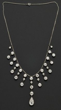Edwardian Diamond Fringe Necklace, bezel-set with thirty-four old European-cut diamonds weighing approx. 13.50 cts., platinum topped gold mounts, later platinum trace link chain, lg. 15 3/4 in.