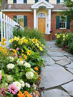 For all-season color, interplant annual flowers with reblooming varieties of perennials. The annuals will keep the garden colorful while the perennials come in and out of bloom. In this walkway border, annuals such as marigold, calendula, and zinnia are teamed with perennial coreopsis and daylily./