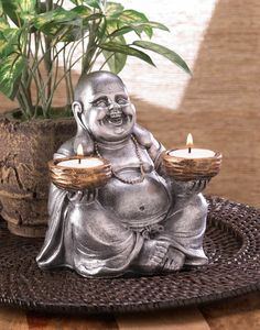 Sitting Buddha Tealight Candle Holder - Illuminate your room with cheerful candlelight with this Sitting Buddha Tealight Candle Holder statue. He will happily sit on your tabletop holding his bronzed candle bowls that are the perfect size for two tealight candles of your choice. His silver finish and smiling face is sure to lend some Zen charm to your decor.