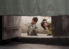 Pakistani children peek under a curtain that hides the residence inside a home of a poor neighborhood in Mingora, in the Swat Valley, Pakistan, Wednesday, November (Photo by Anja Niedringhaus/AP Photo)