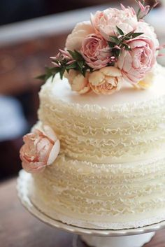ruffled wedding cake with blush floral detailing