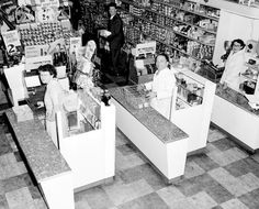 Checkout area of small supermarket with three cash registers and sales assistants. Shelves of canned goods and medicines are visible in background. 1953 Australia