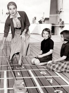 Grace Kelly playing shuffleboard with her nieces on board the S S Constitution en route to Monaco for her wedding, 1956