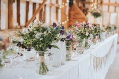 Top Table at The Clock Barn.  Floral design created by Eden Blooms Florist from Nigella, Larkspur, Clematis, Tanancetum Daisy, Bombastic Spray Rose, Pale Blue Delphinium, Stock, Nigella, Rosemary, Mint & Astrantia.  Image by www.tomhalliday.com