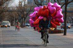 """Feel the Love Around the World -- a man in Beijing almost getting carried away by his balloons while riding a bike."" Click through for more photos. Valentines Day Pictures, Happy Valentines Day, Valentine Pics, Velo Design, Year Of The Dragon, Mylar Balloons, Heart Balloons, Heart Day, Saint Valentine"