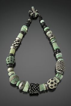 Celadon, Black, and Silver Beaded Bead Necklace by Julie Powell. Beaded beads are created by weaving tiny glass beads one at a time around a wooden bead armature using just a needle and fishing line. Accented with beads of sterling silver, jade, fluorite, onyx, pyrite, pearls, and Czech glass. Handwoven toggle closure. Limited edition of 25.