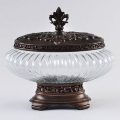 Glass French Quarter Potpourri Jar  Available at Kirkland's for $19.99.  Jar measures 8.25H in. and 12.5 in. in diameter   Crafted of resin and glass   Dark bronze finish  Decorative floral finial top  Clear fluted glass midsection