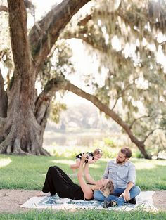 picture of mom and dad playing with baby under a large tree by Valentina Glidden