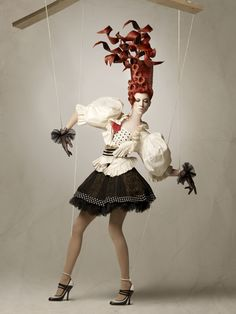 Models/ mannequins attached to strings interacting with artwork.