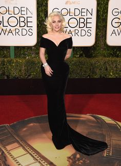 Lady Gaga was pure glamour in custom-made #AtelierVersace. She wore a fitted black velvet gown with exaggerated hips, sweetheart neckline, and off the shoulder sleeves.