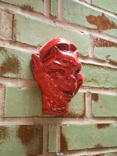 Ceramic devil on custom-glazed brick wall, Frankoma pottery.